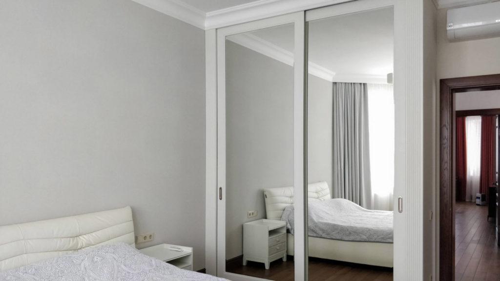 Шкаф с зеркальной поверхностью для расширения пространства в спальне